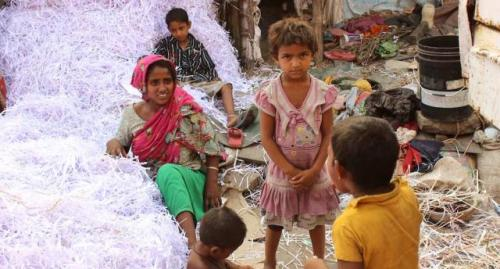 In a roadside ghetto, Akila Bibi and others after a day's hard work, separating white paper shreds from the colored ones for recycling. Earning Rs 3 a kg, they manage 30 kg to 50 kg a day. (Photo by Manipadma Jena)