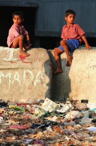 Two boys on a concrete wall, overlooking rubbish in Dharavi, Asia's largest slum and home to hundreds of businesses defying the myths about poverty. By- NGO MEDAPT