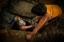 Kaverappa being lifted out of a pit by Muniraju in Bengaluru. By: Water Aid / CS Sharada Prasad